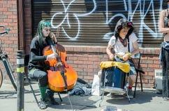 De straatkunstenaars spelen op instrumenten bij Farmer' s Markt Stock Foto