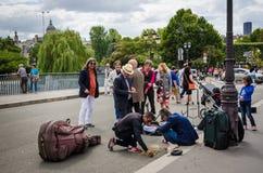 De straatmusici tellen hun muntstukken na het presteren op Pont-Saint Louis in Parijs Stock Foto's