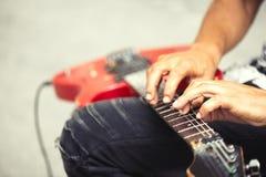De straatmusicus speelt elektrische gitaar met zijn vingers in dia stock fotografie