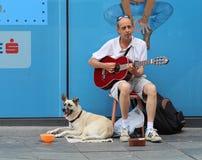 De Straatmusicus van Zagreb/Gitaarspeler met Hond stock afbeeldingen