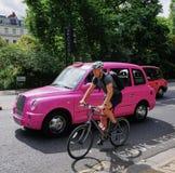 De straatsc?ne van Londen met ongebruikelijke roze klassieke cabine en fietser stock foto's