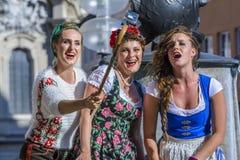 De straatuitvoerders, kleedden zich in Beierse traditionele kostuums, binnen Stock Foto