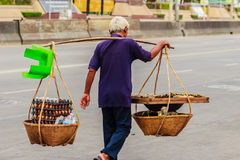 De straatventer loopt met draagt bamboemanden van geroosterd b.v. Stock Foto's