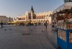 De straatventer van Obwarzanekkrakowski in het belangrijkste marktvierkant met Doekzaal op de achtergrond, Krakau, Polen stock foto's