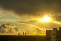 De stralen die van de zon door de onweerswolken op de rand van de stad breken stock afbeelding