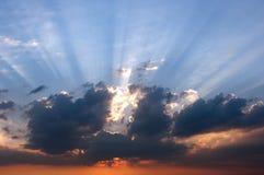 De stralen van de het plaatsen zon achter de wolken Stock Afbeeldingen