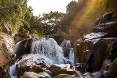 De stralen van de het plaatsen zon op de waterval Bajo Stock Afbeeldingen