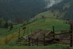 De stralen van de ochtendzon in het huis van mistbergen Stock Afbeelding
