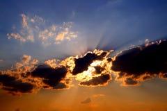 De stralen van de zon achter donkere wolken in hemel Stock Fotografie