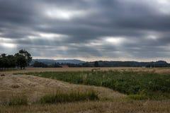 De stralen van de zon die door de donkere wolken gaan Stock Fotografie