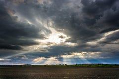 De stralen van de zon die van de wolken barsten Stock Foto