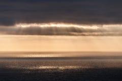 De stralen van de zon doordringen de wolken en vallen aan de Atlantische Oceaan, zich uitrekt aan de horizon Stock Foto