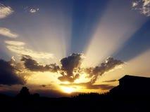 De stralen van de zon tussen wolken, bij schemer stock fotografie