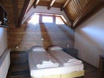 De stralen van licht doordringen de comfortabele houten slaapkamer stock afbeeldingen