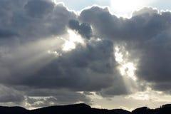 De stralen van de zon glanzen trog donkere wolken Stock Afbeelding
