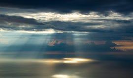 De stralen van zonlicht maken hun manier door de wolken, die het overzees verlichten stock foto