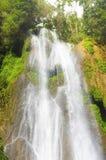 De stralendaling van het watervalwater van een hoogte tussen rotsen en vegeta Royalty-vrije Stock Foto's