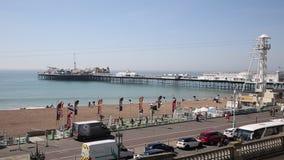 De strandboulevardstrand en pijler van Brighton met mensen in mooi weer stock videobeelden