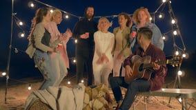 De stranddansen, bedrijf wordt van de jeugd onderhouden en op snaarinstrument op kust in verlichting van lampen gespeeld stock videobeelden