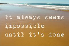 De strandscène van nat zand met golven in de achtergrond en het motievencitaat het altijd schijnt onmogelijk tot het gedaane ` s stock afbeeldingen