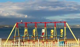 De strandschommeling ligt ongebruikt als zonreeksen over het strand Royalty-vrije Stock Foto