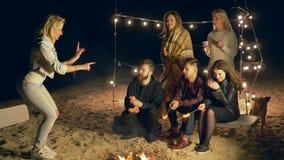 De strandspelen, de jeugd spelen in vrolijk vermaak tijdens picknick door brand in zand stock video