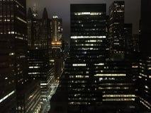 De Straten van New York met een stroom van auto's en hoog aangestoken wolkenkrabbers tegen de nachthemel stock afbeeldingen