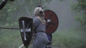 De strijd op het slagveld, mensen in pantser vecht met zwaarden stock videobeelden