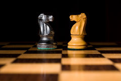 De strijd van twee schaakridders op schaakbord Stock Afbeeldingen