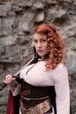 De strijdersvrouw met zwaard in middeleeuwse kleren is zeer gevaarlijk Royalty-vrije Stock Foto's