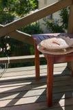 De strohoed ligt op eenvoudige houten kruk De kruk bevindt zich op klein open balkon royalty-vrije stock afbeelding