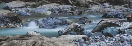 De stromen van het rivierwater over stenen Royalty-vrije Stock Foto's