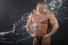 De stromen van het water op ongeklede bodybuilder Royalty-vrije Stock Foto