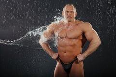 De stromen van het water op ongeklede bodybuilder Royalty-vrije Stock Afbeeldingen