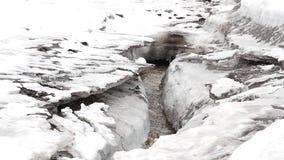 De stromen van de de lentekreek onder grijze blokken van ijs stock footage