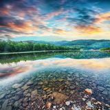 De stroom van de bergrivier van water in de rotsen met majestueuze zonsondergang royalty-vrije stock afbeelding