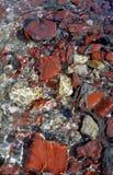 De stroom van het water met rode rotsen Stock Afbeeldingen
