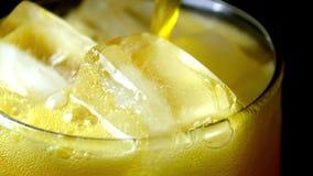 De stroom van soda die gietend in een glas met ijsblokje op een zwarte achtergrond, close-uptextuur, het bespatten, plons, bruist stock videobeelden