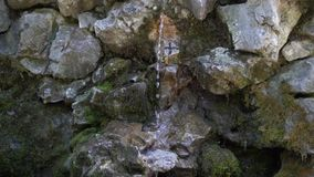 De stroom van vers koud die water van de de lentedalingen door oude stenen worden omringd stock footage