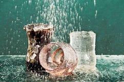 De stroom van water giet in het gekleurde glas. Stock Foto's