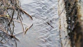 De stroom van water valt van de houten gang aan het waterwiel stock videobeelden