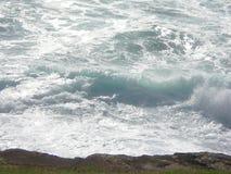 De stroomversnelling van het breken van golven op een rotsplank Stock Foto