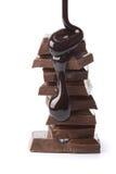 De stroop die van de chocolade op chocoladestukken wordt gegoten Royalty-vrije Stock Fotografie