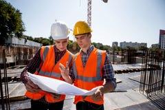De structurele ingenieur en de bouwmanager gekleed in oranje het werkvesten en helmen bespreken documentatie op open royalty-vrije stock foto