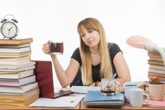 De student bereidt een thesisproject bij nacht voor en dronk een andere kop van koffie Stock Fotografie