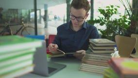 De student bestudeert met vele boeken op de lijst in de bibliotheek stock video