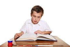 De student die van de school een boek leest. stock foto
