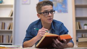 De student die van de tienercollage taak voorbereiden, lerend vreemde taal, woordenschat stock video