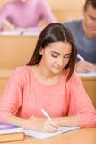 De student is het bezige schrijven in haar handboek stock fotografie