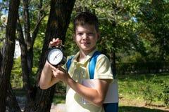 De student in het park houdt een wekker, tijd terug naar school, over is de vakantie royalty-vrije stock afbeeldingen